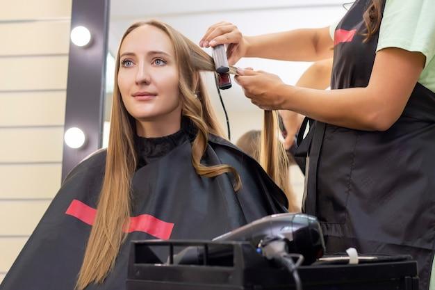 Женский парикмахер, салон красоты. парикмахер делает кудри плойкой