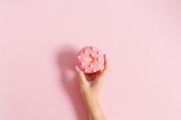 Женская рука держит пончик на розовом фоне