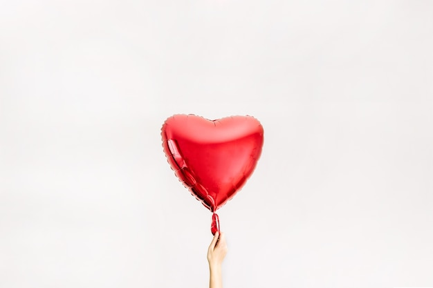 Womens hand holding red heart shape balloon. love concept