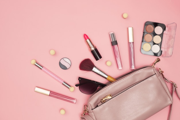 Womens handbag with cosmetics, makeup tools and accessories on pink background, beauty, fashion, shopping concept, flat lay. high quality photo