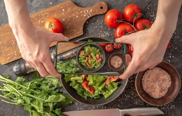 女性の手が写真を撮るために野菜サラダの上に携帯電話を持っています