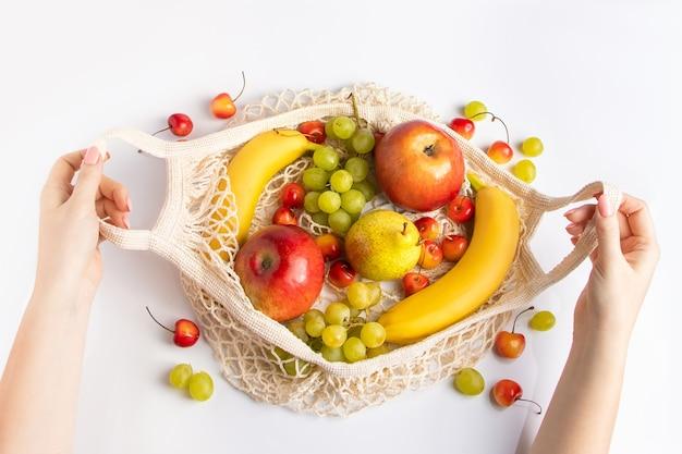 Женские руки держат экологически чистый сетчатый мешок с фруктами. органическая веганская еда.