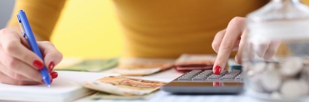 여자의 손에 펜을 들고 계산기에 지폐를 세고 있습니다. 예산 계획 개념