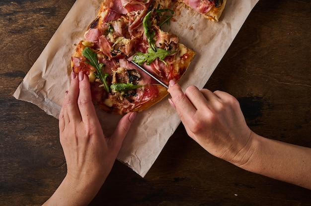 Womens hands cut with knife rectangular roman pizza with prosciutto ham tomatoes mozzarella