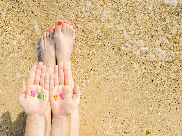 Womens hands and feet with a red pedicure against the sea sand and surf in the palms of the letters with the inscription happy holiday vacation copy space