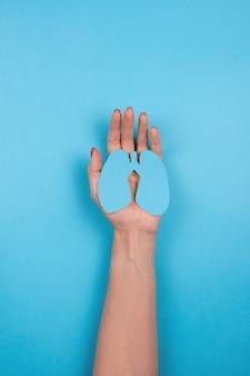 여성의 손은 세계 결핵의 날 또는 치유의 파란색 배경 개념에 종이 폐 기호를 들고...