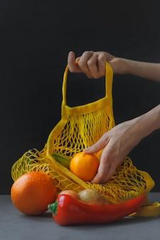 여자의 손을 잡고 어두운 배경에 야채와 함께 문자열 가방