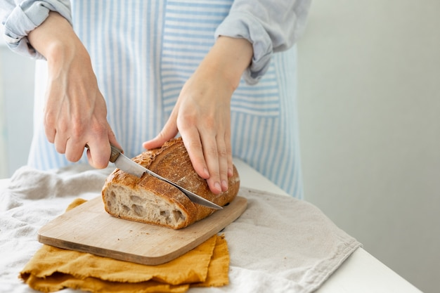 女性の手は軽いエプロンの背景にパンを保持します