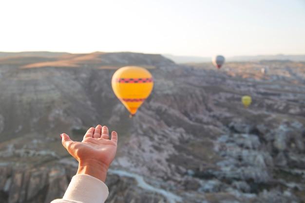 トルコのカッパドキアの休日の空に飛んでいる風船を背景にハートの形をした女性の手がパンデミックの最中に旅行します