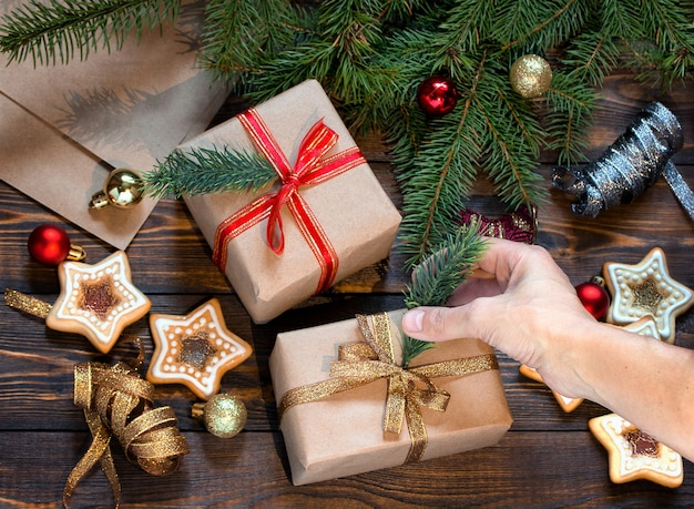 女性の手は自家製のクッキーとクリスマスツリーのおもちゃと木製のテーブルにクリスマスプレゼントを詰める