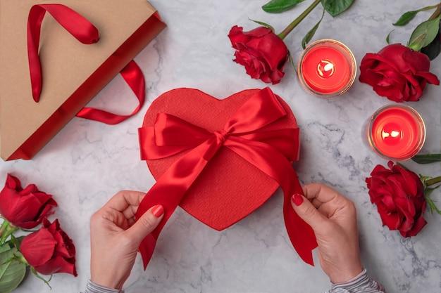 Женские руки касаются красного атласного банта на картонной подарочной коробке в форме сердца