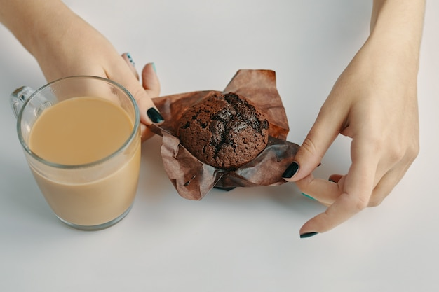 Womens hands unwrap chocolate muffin mug of coffee on white table morning romantic breakfast cocoa a...