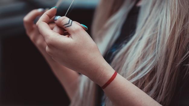 指に矢印、手首に赤い線のある女性の手-入れ墨