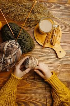 Женские руки с клубком пряжи кофе и тростника на деревянном фоне руки в оранжевом свитере ремесло хо ...