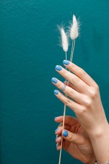 ターコイズブルーの背景のクローズアップに青いマニキュアと女性の手