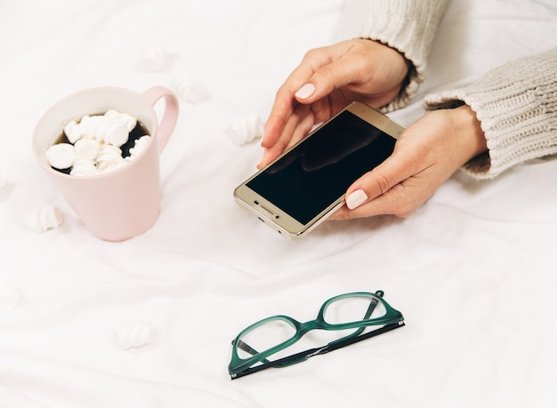 Womens hands with phone, coffee and glasses