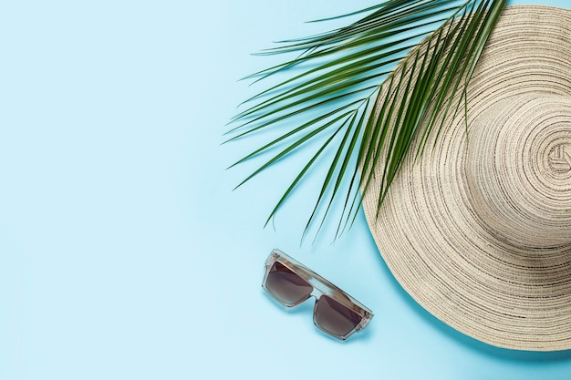 Womens hat with wide brim, sunglasses and a branch of a palm tree on a blue background.