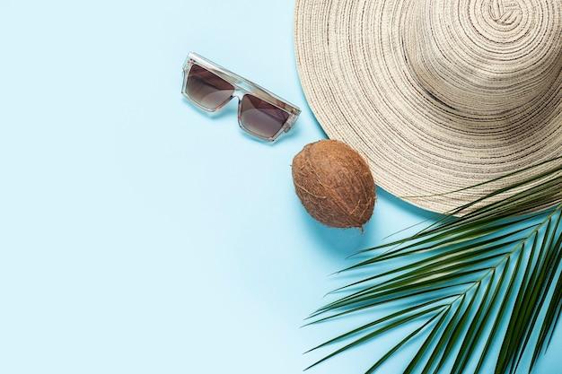 青い背景に広いつば、サングラス、ココナッツ、ヤシの木の枝を持つ女性用の帽子。