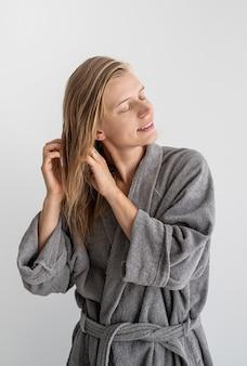 Женское здоровье. спа и велнес. счастливая молодая женщина, применяя маску для волос в ванной комнате