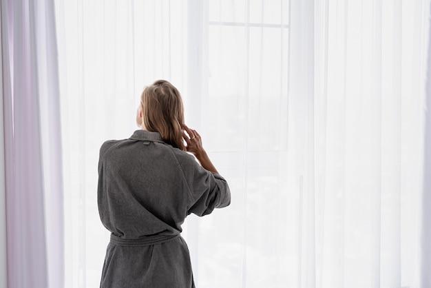Женское здоровье. спа и велнес. счастливая молодая женщина, применяя маску для волос, стоя рядом с окном. вид сзади