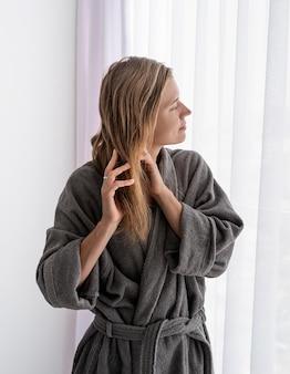 Женское здоровье. спа и велнес. счастливая молодая женщина, применяя маску для волос, стоя рядом с окном