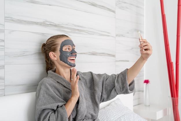 女性の健康。スパとウェルネス。モバイルデバイスを使用してベッドに座ってリラックスしたフェイスマスクを持つ女性