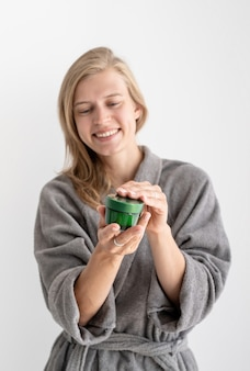 Женское здоровье. спа и велнес. молодая улыбающаяся женщина, держащая бутылку с косметическим продуктом