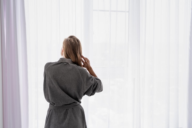 Womens health. spa and wellness. happy young woman applying hair mask standing next to the window. rear view