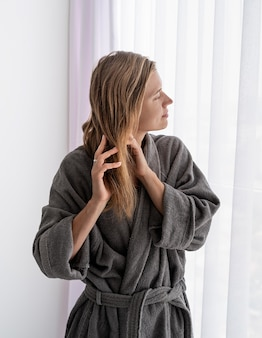 Womens health. spa and wellness. happy young woman applying hair mask standing next to the window