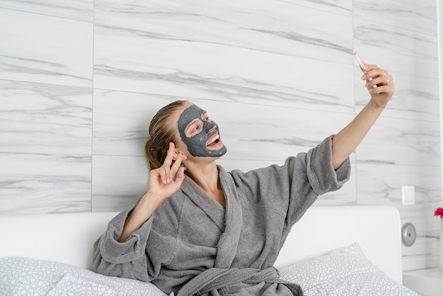 Womens health. spa and wellness. woman with face mask relaxing sitting on the bed using mobile device