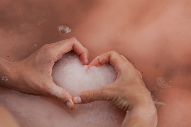 Womens heartshaped hands hold pink salt on water surface of unique pink lake