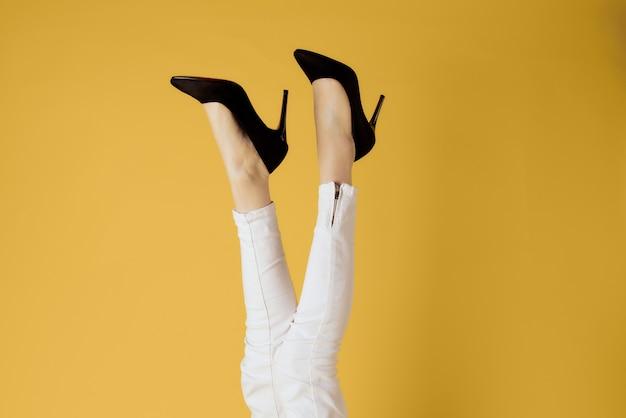 Женские перевернутые ноги и черные туфли белые джинсы изолированные