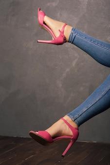 インテリアにハイヒールのピンクのサンダルの女性の足