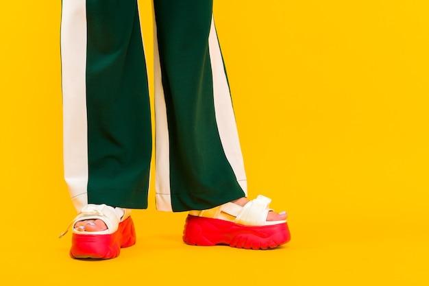赤い靴底と縞模様の緑のズボンとスポーツサンダルの女性の足