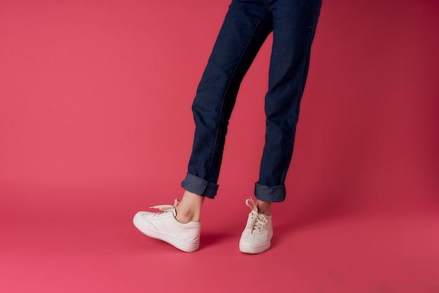 여자 다리 청바지 흰색 운동화 거리 패션 스튜디오 분홍색 배경. 고품질 사진