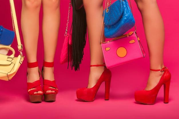 여자 다리. 인식 할 수없는 여성은 가방과 지갑을 들고 있습니다. 분홍색 벽에 빨간 신발을 착용하는 숙 녀.