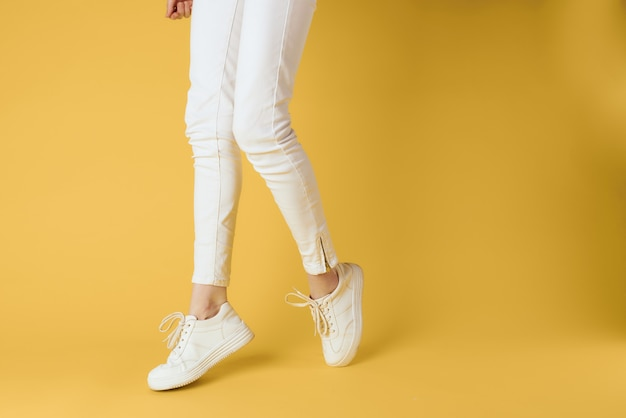 レディースレッグスホワイトパンツスニーカーファッション服高級ストリートスタイル黄色の背景。高品質の写真