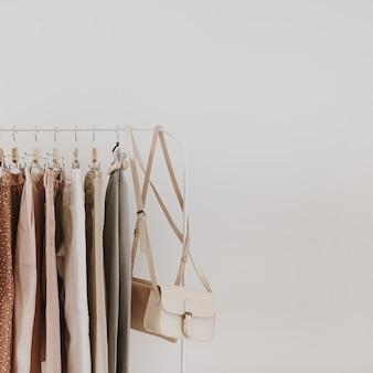 レディースミニマルファッションパステル服。スタイリッシュな女性のブラウス、セーター、パンツ、ジーンズ、tシャツ、白のハンガーのハンドバッグ