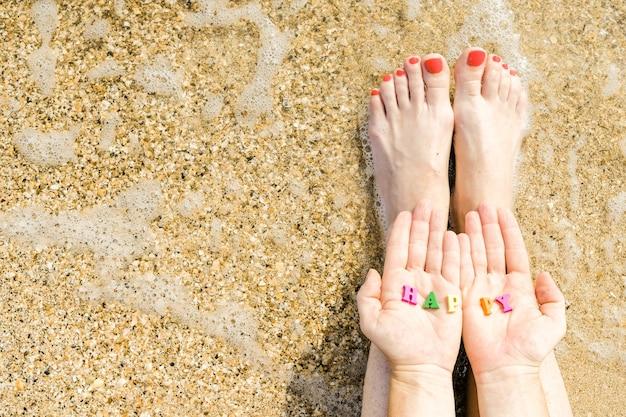 Женские ладони с надписью happy на фоне морского песка и прибоя