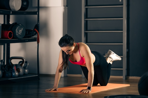 Женские отжимания во время занятий фитнесом в тренажерном зале