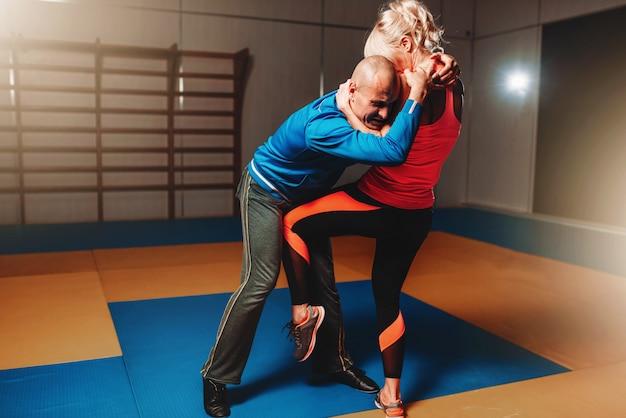インストラクターと一緒の女性の自己防衛トレーニング