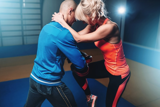 Womens self defense workout with personal instructor, fighting training in gym, martial art
