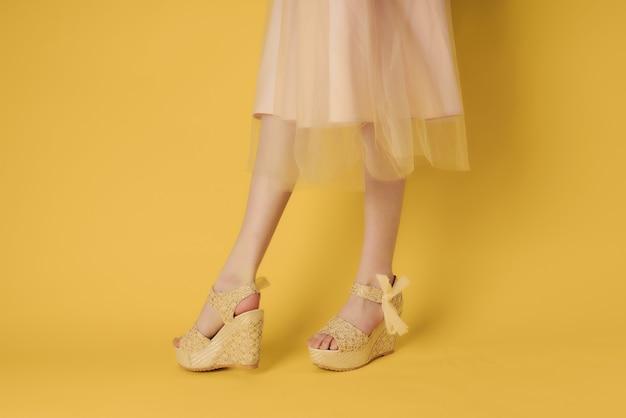 レディースシューズベージュ黄色の背景ポーズファッション