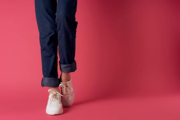 ピンクの背景のポーズの女性の靴のトリミングされたビュー