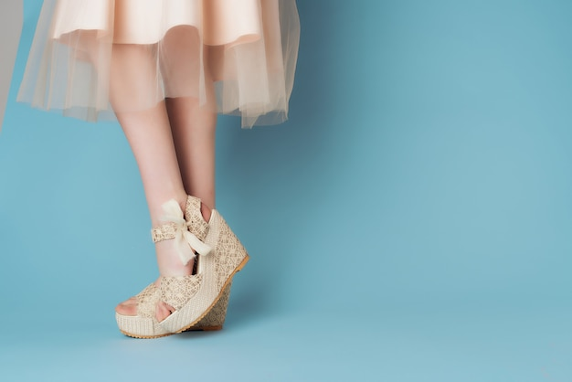トリミングされたビュー青い背景モダンなスタイルのポーズをとる女性の夏の靴