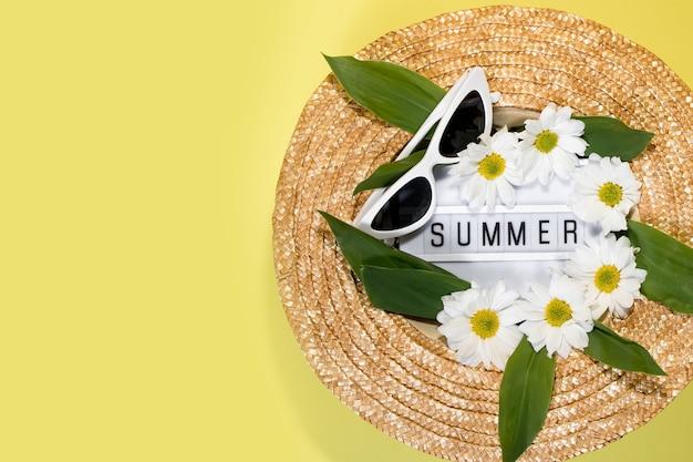 黄色の背景の上の女性の夏の麦わら帽子平面図フラットレイコピースペース夏の旅行休暇共同