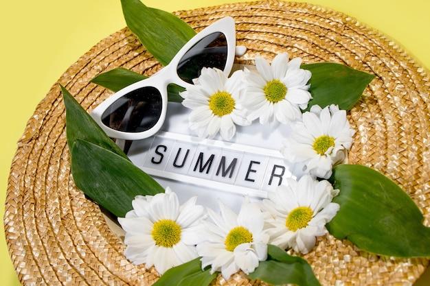 黄色の背景の上の女性の夏の麦わら帽子平面図フラットレイコピースペース。夏の旅行休暇のコンセプト、単品。黄色の背景に文字とフィールドカモミールの花からsummerにテキストを送信します。