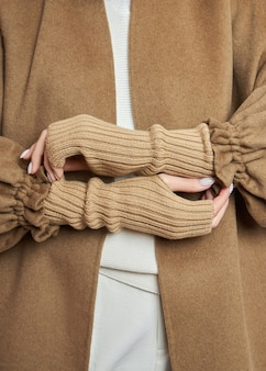 Женские руки в теплых зимних варежках. осенняя одежда. красивый маникюр на ногтях