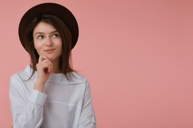 不思議な女性、長いブルネットの髪の美しい少女。白いブラウスと黒い帽子をかぶっています。彼女のあごに触れてください。感情的な概念。パステルピンクの壁の上のコピースペースで右を見て