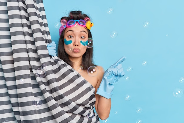Wondered beautiful woman with eastern appearance enjoys morning routine procedure takes shower in bathroom at home indicates at blank empty space makes hairstyle isolated on blue background.